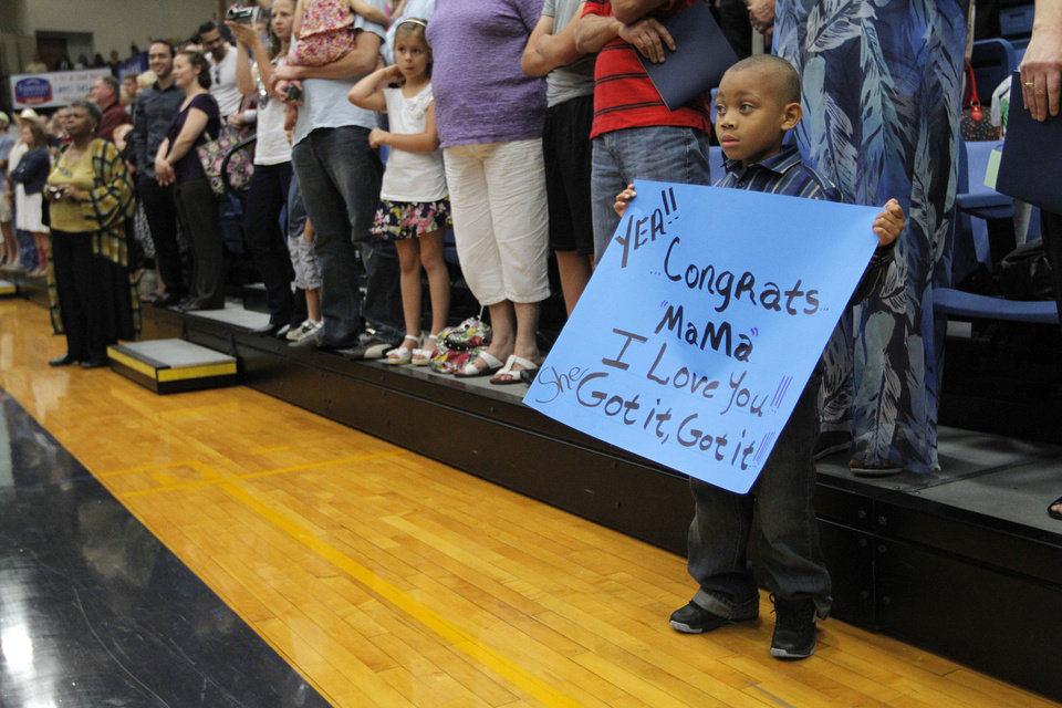 Photo - K'Vion Berry, 5, of Oklahoma City, holds a sign for his mother, Tamara, during a University of Central Oklahoma graduation ceremony in Edmond, Friday, May 4.  Photo by Garett Fisbeck, For The Oklahoman