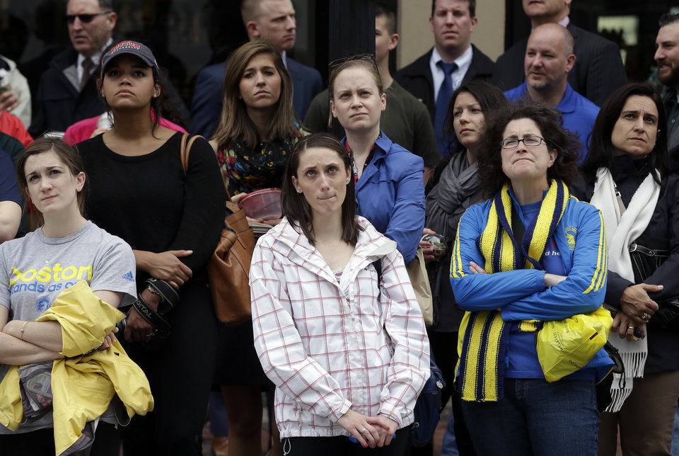 Photo - Heather McDade, of Boston, center, reacts while watching a tribute ceremony with others on an over-sized outdoor monitor, Monday, April 14, 2014, on Boylston Street, in Boston. The ceremony is being held for those killed and injured in the bombings at the finish line of the Boston Marathon a year ago. (AP Photo/Steven Senne)