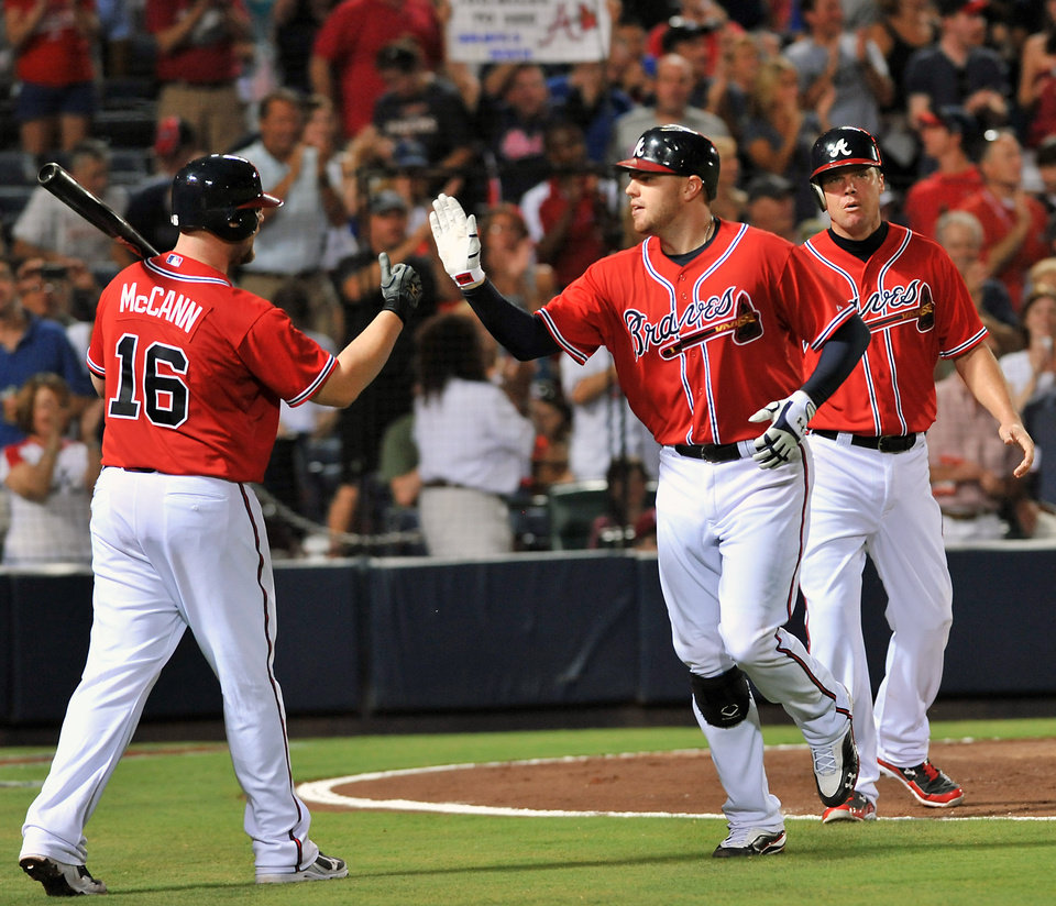 Photo -   Atlanta Braves' Freddie Freeman, center, celebrates with teammates Brian McCann (16) and Chipper Jones, right, after hitting a two-run home run against the Philadelphia Phillies during the fifth inning of a baseball game on Friday, Aug. 31, 2012, at Turner Field in Atlanta. (AP Photo/Gregory Smith)