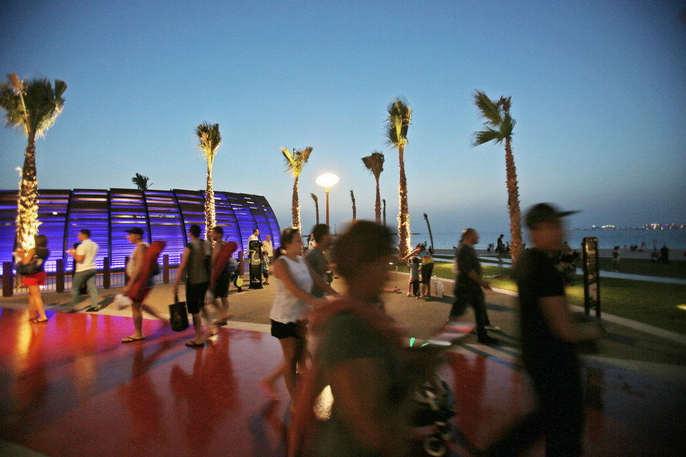 Photo - In this Monday, April 21, 2014 photo, people walk past a gym at the beach in Dubai, United Arab Emirates. The beach _ which overlooks the city's iconic Palm Jumeirah island, far right, is now more popular than ever after the recent opening of a sleek new shopping and entertainment promenade. (AP Photo/Kamran Jebreili)
