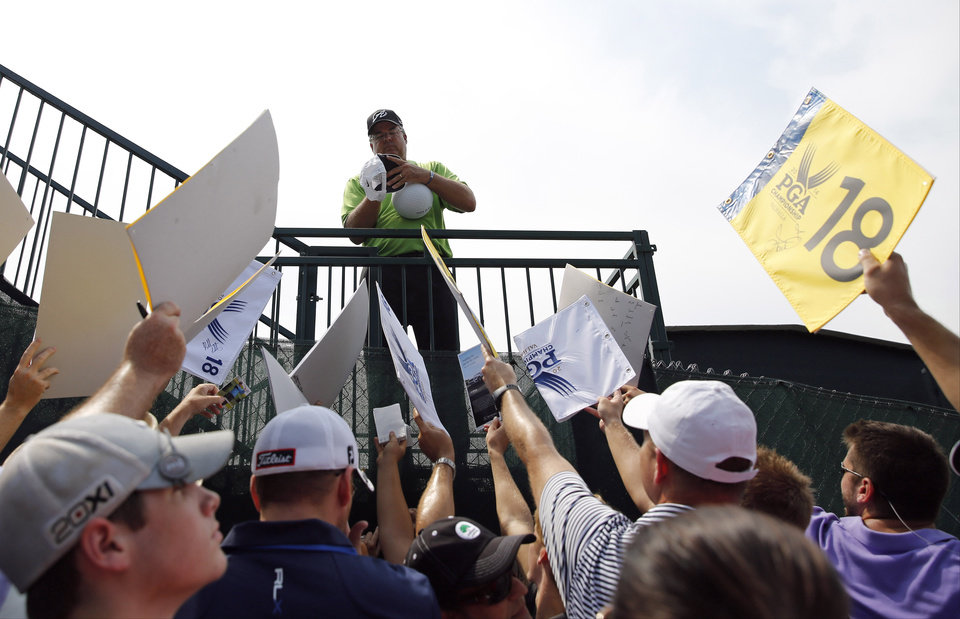 Photo - Kenny Perry signs autographs after a practice round for the PGA Championship golf tournament at Valhalla Golf Club on Tuesday, Aug. 5, 2014, in Louisville, Ky. The tournament is set to begin on Thursday. (AP Photo/Jeff Roberson)