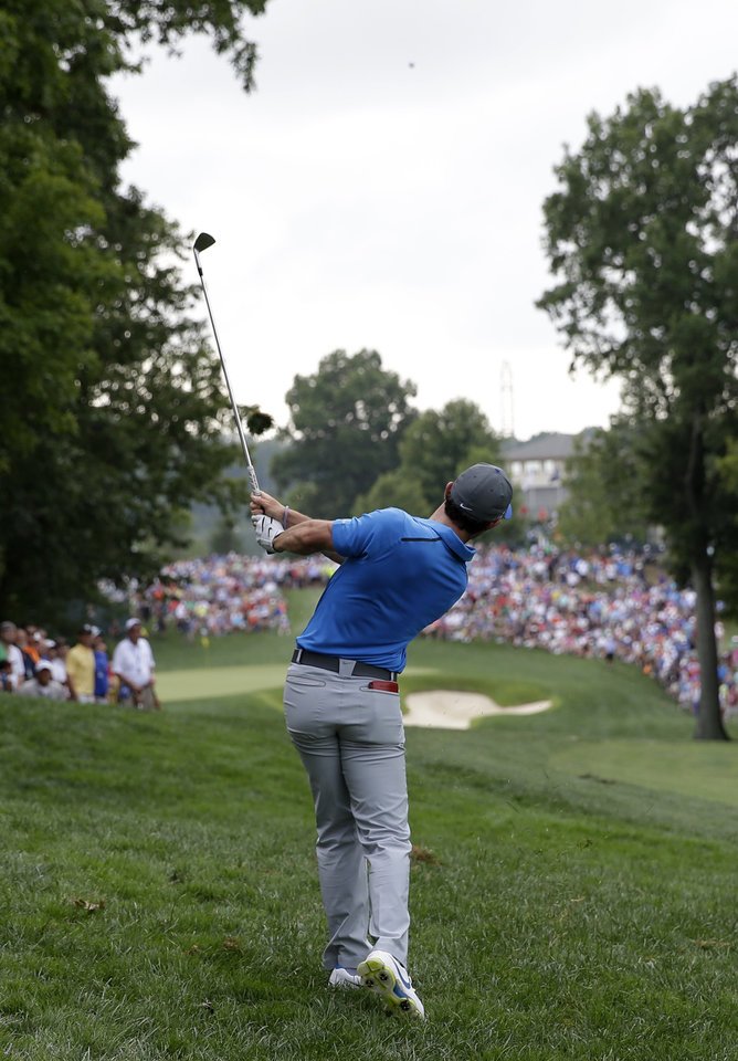 Photo - Rory McIlroy, of Northern Ireland, hits from rough on the 12th hole during the third round of the PGA Championship golf tournament at Valhalla Golf Club on Saturday, Aug. 9, 2014, in Louisville, Ky. (AP Photo/David J. Phillip)