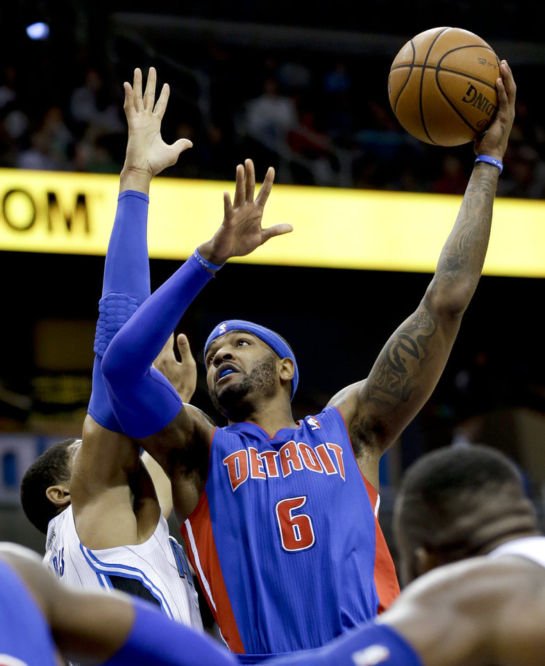 Photo - Detroit Pistons' Josh Smith (6) shoots over Orlando Magic's Tobias Harris, left, during the first half of an NBA basketball game in Orlando, Fla., Friday, Dec. 27, 2013. (AP Photo/John Raoux)