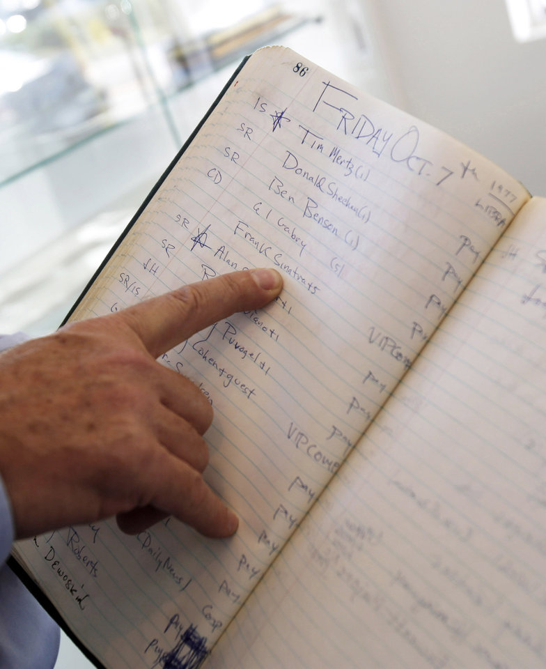This Jan. 16, 2013 photo shows a finger pointing to the name Frank Sinatra in a reservation book for the famed New York Studio 54 night club in West Palm Beach, Fla. Memorabilia from the famed 1970s club is hitting the auction block in Florida. The private collection of co-founder Steve Rubell is being sold Saturday in West Palm Beach. (AP Photo/Alan Diaz)