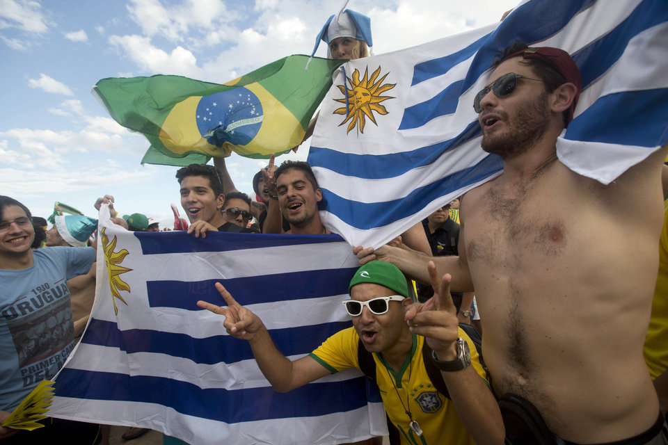 Photo - Brazil and Uruguay soccer fans wave their flags as they gather for the start of the World Cup soccer game between Brazil and Croatia inside the FIFA Fan fest area on Copacabana beach in Rio de Janeiro, Brazil, Thursday, June 12, 2014. (AP Photo/Silvia Izquierdo)