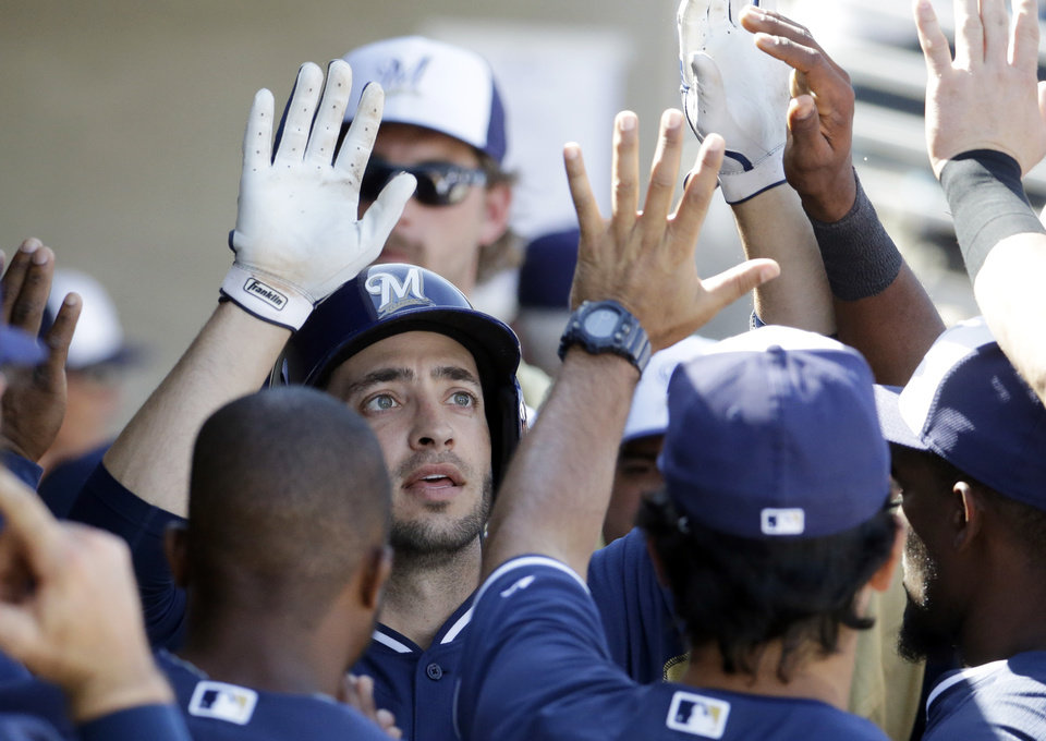 Photo - Milwaukee Brewers' Ryan Braun is congratulated by teammates after hitting a home run during the eighth inning of an exhibition baseball game against the Oakland Athletics on Wednesday, March 5, 2014, in Phoenix. (AP Photo/Morry Gash)