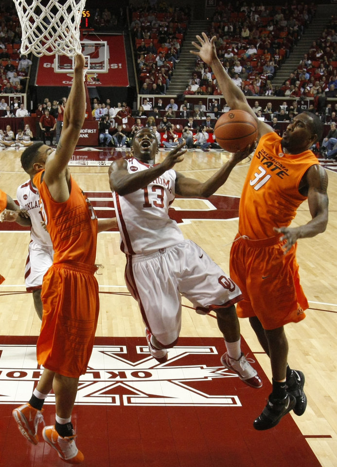 Photo - OU's Willie Warren (13) is fould by OSU's Matt Pilgrim (31) under the basket during the first half of the college bedlam basketball game between The University of Oklahoma Sooners (OU) and Oklahoma State University University Cowboys (OSU) at the Lloyd Noble Center on Monday, Jan. 11, 2010, in Norman, Okla.