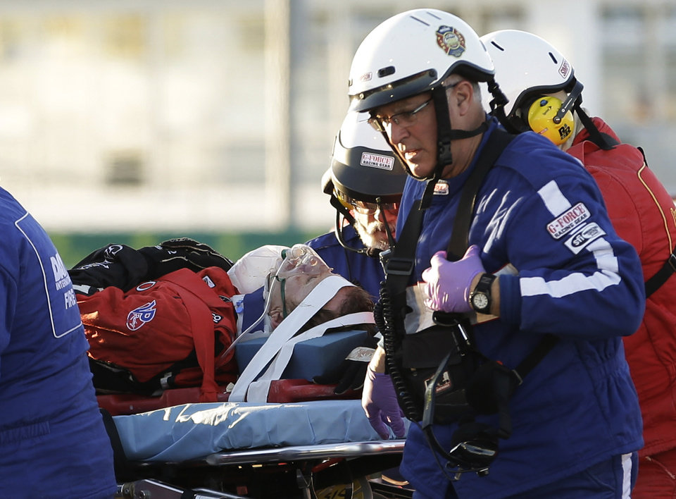 Photo - Rescue workers move driver Memo Gidley, center, to an ambulance after he was involved in a crash during the IMSA Series Rolex 24 hour auto race at Daytona International Speedway in Daytona Beach, Fla., Saturday, Jan. 25, 2014. (AP Photo/John Raoux)