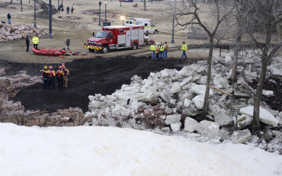 Photo - Emergency crews on scene  Friday, March 15, 2013, work to recover the bodies of two adults that went into the Big Sioux River to rescue a 6-year-old boy that fell into the water at Falls Park Thursday evening in Sioux Falls, S.D. Sioux Falls Fire Chief Jim Sideras said early Friday a woman who a relative of the boy's but not his mother jumped into the water to try to save the boy, and a man jumped in to try to save the woman and child. The boy emerged from the water a short time later downstream at Falls Park, and was not injured.  (AP Photo/Argus Leader, Elisha Page) NO SALES