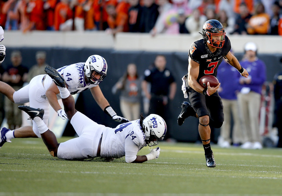 Photo - Oklahoma State's Spencer Sanders (3) gets by TCU's Colt Ellison (44) and Corey Bethley (94) during the college football game between the Oklahoma State University Cowboys and the TCU Horned Frogs at Boone Pickens Stadium in Stillwater, Okla.,  Saturday, Nov. 2, 2019. OSU won 34-27. [Sarah Phipps/The Oklahoman]