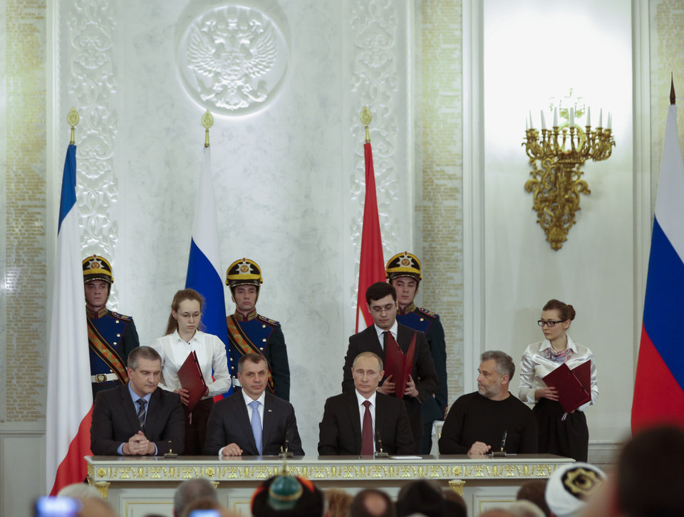 Photo - Russian President Vladimir Putin, second right, Speaker of Crimean parliament Vladimir Konstantinov, second left, Crimean Premier Sergei Aksyonov, left, and Sevastopol mayor Alexei Chalyi, right, sit during a signing ceremony for the treaty to join Crimea with Russia in the Kremlin, Moscow, Tuesday, March 18, 2014. President Vladimir Putin on Tuesday signed a treaty to incorporate Crimea into Russia, describing the move as the restoration of historic injustice and a necessary response to what he called the Western encroachment on Russia's vital interests. (AP Photo/Alexander Zemlianichenko)