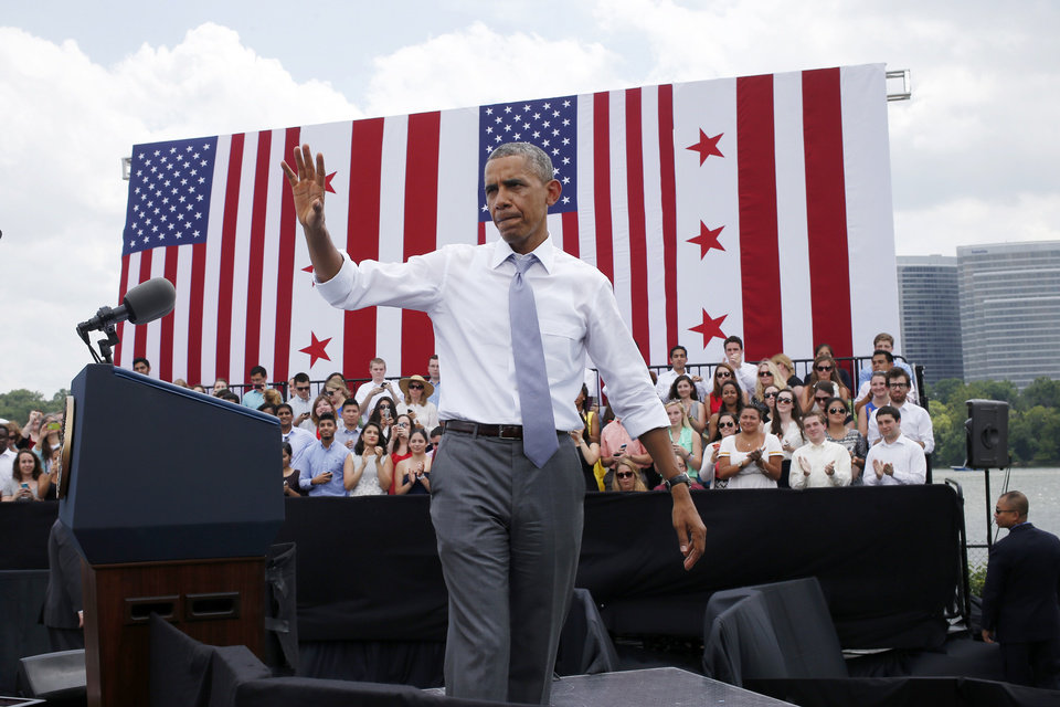 Photo - President Barack Obama waves after his remarks about transportation and the economy, Tuesday, July 1, 2014, at Georgetown Waterfront Park in Washington. The president said 700,000 jobs could be at risk next year if Congress doesn't quickly agree on how to pay for highway and transit programs.  (AP Photo/Charles Dharapak)
