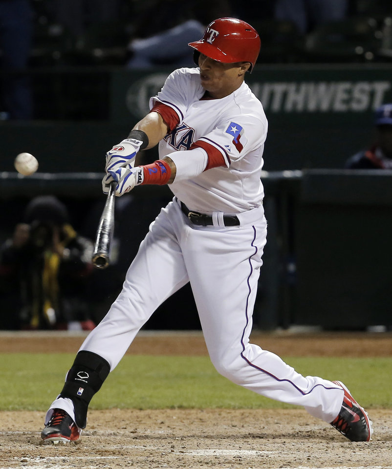 Photo - Texas Rangers' Leonys Martin makes contact for an RBI-single to the ninth inning of a baseball game against the Seattle Mariners, Wednesday, April 16, 2014, in Arlington, Texas. Texas won 3-2. (AP Photo/Brandon Wade)