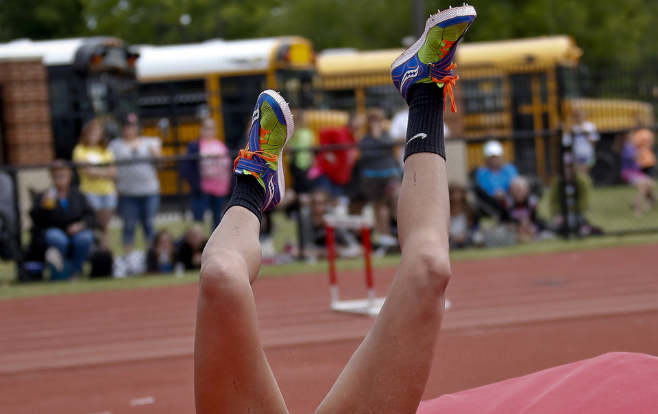 Photo - A competitor's feet go in the air as she hits the mat while taking part in the Class 5A girls high jump during the Class 6A and 5A state championship track meet at Yukon High School on Saturday, May 17, 2014 in Yukon, Okla.   Photo by Chris Landsberger, The Oklahoman