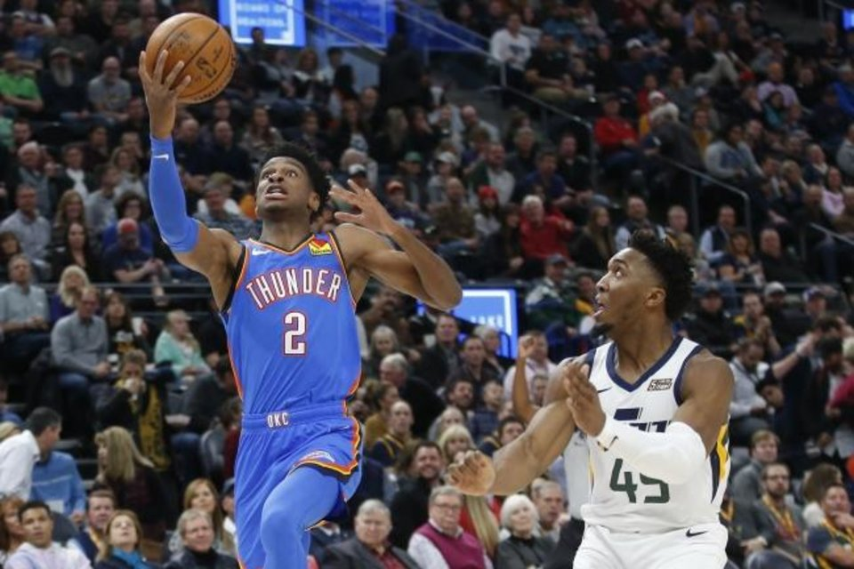 Photo -  Oklahoma City Thunder guard Shai Gilgeous-Alexander, left, goes to the basket as Utah Jazz guard Donovan Mitchell looks on during Monday night's game in Salt Lake City. [AP Photo/Rick Bowmer]