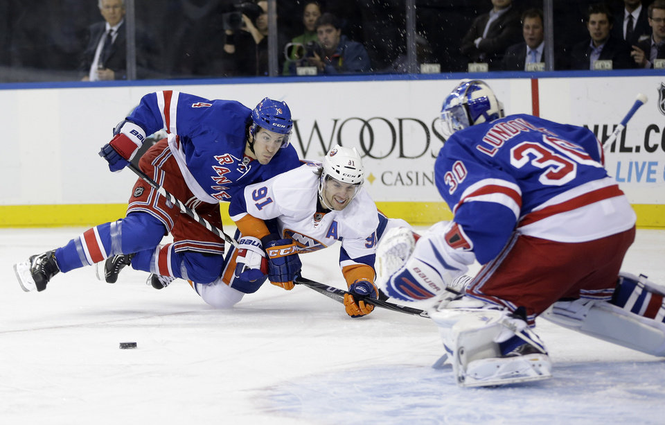 New York Rangers' Michael Del Zotto, left, becomes entangled with New York Islanders' John Tavares, center, as he attempts a shot on New York Rangers goalie Henrik Lundqvist, right, during the first period of the NHL hockey game in New York, Thursday, Feb. 7, 2013. (AP Photo/Seth Wenig)