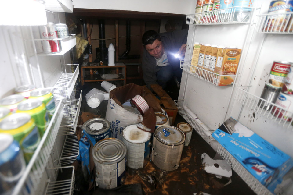 Photo - Noel McKenna uses a flashlight to sort through a closet as he helps the Colabella family clean up their home, which was flooded in the wake of Superstorm Sandy, Thursday, Nov. 1, 2012, in Brick, N.J. Sandy, the storm that made landfall Monday, caused multiple fatalities, halted mass transit and cut power to more than 6 million homes and businesses. (AP Photo/Julio Cortez) ORG XMIT: NJJC107