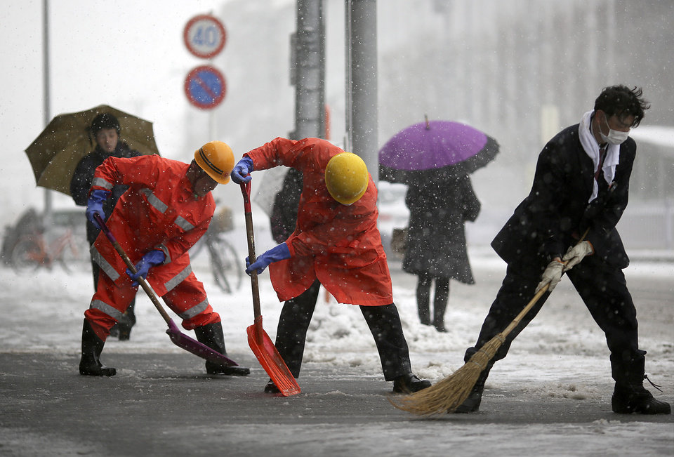 Photo - Railway station workers shove snow from the street in Yokohama, Japan, Saturday, Feb. 8, 2014.  The Japan Meteorological Agency issued the first heavy snowfall warning for central Tokyo in 13 years. Some 20-centimeter (7.9-inch) of snowfall is expected by Sunday morning in the metropolitan areas. (AP Photo/Eugene Hoshiko)