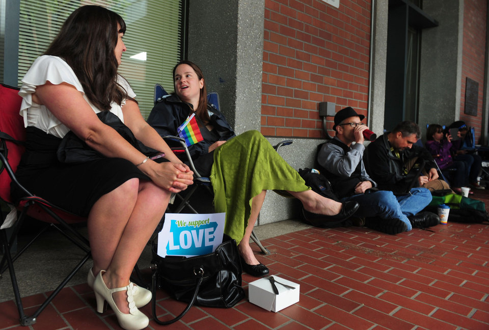 Photo - From left, Julia Fraser, Jessica Rohrbacher, Ken Brashier and Andrew Wallace pass the time in front of the Multnomah County Recorder's building in Portland, Or. on Monday, May. 19, 2014. They are awaiting a ruling in the Marriage Equality case, so they can go into the building and get their marriage licenses. A ruling in that case is expected on Monday. (AP Photo/Steve Dykes)