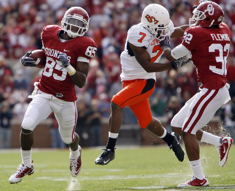 Photo - Oklahoma's Ryan Broyles (85) gets a block from Jamell Fleming (32) on an Oklahoma State defender during the first half of the Bedlam college football game between the University of Oklahoma Sooners (OU) and the Oklahoma State University Cowboys (OSU) at the Gaylord Family-Oklahoma Memorial Stadium on Saturday, Nov. 28, 2009, in Norman, Okla.