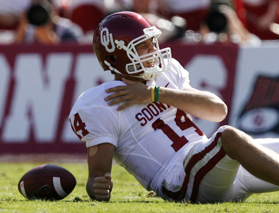 Photo - Sam Bradford reacts after being sacked by Texas in the first quarter during the Red River Rivalry college football game between the University of Oklahoma Sooners (OU) and the University of Texas Longhorns (UT) at the Cotton Bowl in Dallas, Texas, Saturday, Oct. 17, 2009. Photo by Chris Landsberger, The Oklahoman