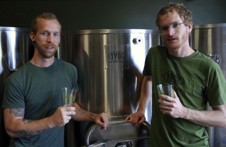 Photo - In a Wednesday, Aug. 14, 2013 photo, Young Veterans Brewing Co. President Thomas Wilder, left,  and head brewer Neil McCanon pose for a photo with glasses of ¬¨¬®a¬®Jet Noise IPA,¬¨¬®aaÜ at the Virginia Beach, Va., brewery. The two Iraq War veterans are set to open the brewery in military-heavy Hampton Roads in September. Virginia, which is celebrating its second craft beer month in August, has seen the industry grow from about 40 craft breweries last year to more than 60 in 2013, with countless more in the works. (AP Photo/Michael Felberbaum) ORG XMIT: RIC101