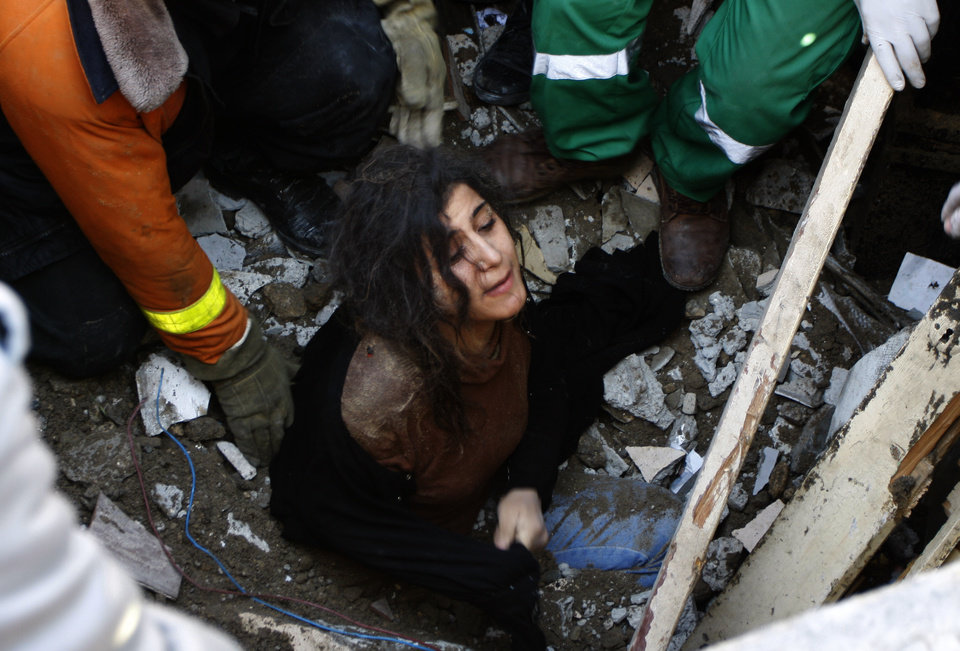 Photo -   A member of the Abdel Aal family is rescued after his family house collapsed during an Israeli forces strike in the Tufah neighbourhood, Gaza City, Sunday, Nov. 18, 2012. The Israeli military widened its range of targets in the Gaza Strip on Sunday to include the media operations of the Palestinian territory's Hamas rulers, sending its aircraft to attack two buildings used by both Hamas and foreign media outlets. (AP Photo/Majed Hamdan)