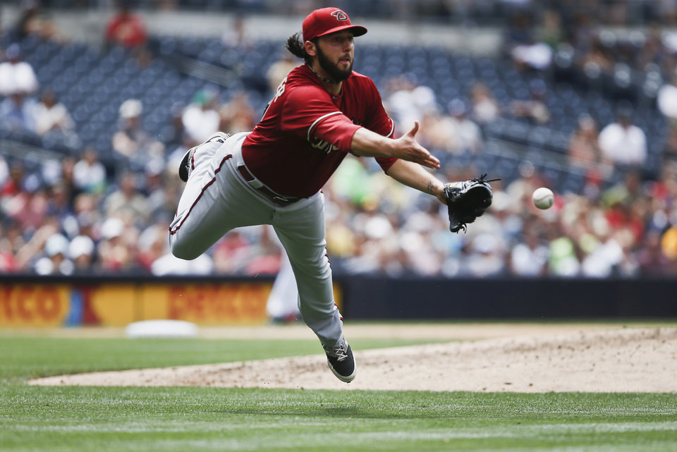 Photo - Arizona Diamondbacks starting pitcher Mike Bolsinger throws out San Diego Padres' Yasmani Grandal at first after recovering from a line drive that hit him while on the mound during the sixth inning of a baseball game  Sunday, June 29, 2014, in San Diego.  (AP Photo/Lenny Ignelzi)
