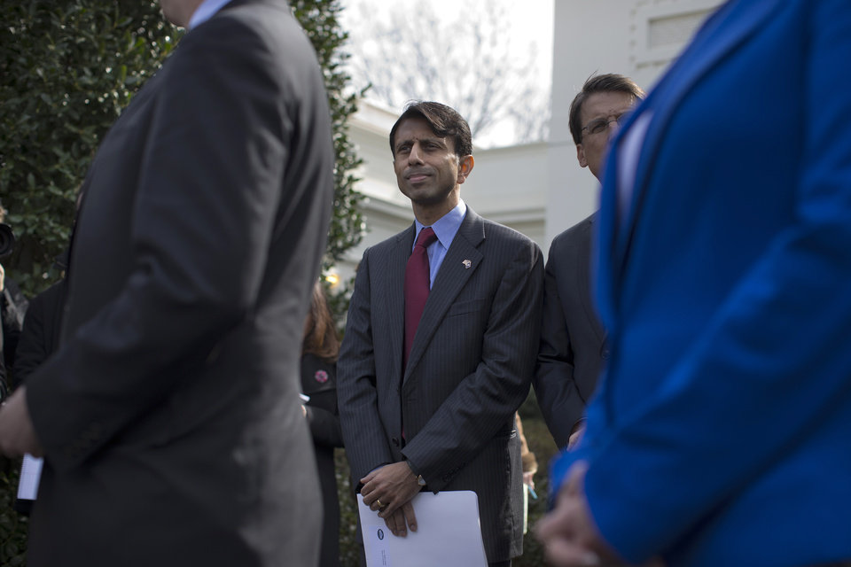 Photo - Louisiana Gov. Bobby Jindal listens as National Governors Association Chairman, Delaware Gov. Jack Markell, speaks with reporters outside the White House in Washington, Monday, Feb. 25, 2013, following their meeting with President Barack Obama. (AP Photo/Evan Vucci)