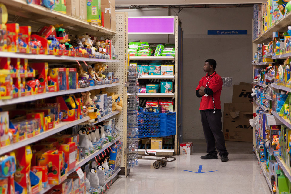 """Jacoby Greer, 18, stands in a corner of Toys """"R"""" Us to direct Black Friday shoppers in Flint, Mich. on Thursday, Nov. 22, 2012. """"I'm a little nervous,"""" Greer admitted feeling his first time working during Black Friday, """"It's a lot of people."""" (AP Photo/Flint Journal, Griffin Moores)"""