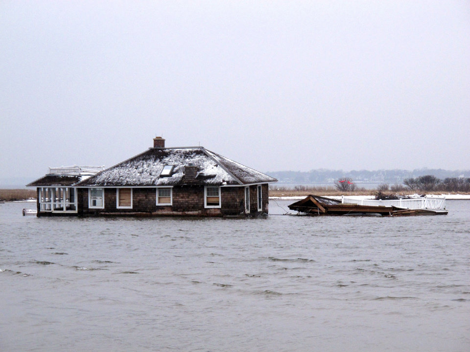 This Feb. 5, 2013, photo,shows a home in the middle of Barnegat Bay, that was washed into the Bay from Mantoloking N.J. during Superstorm Sandy. States hit hard by Sandy are gearing up to remove tons of debris from waterways, including houses, vehicles, sunken boats, furniture, pieces of piers, decks and bulkheads _ all of which must be removed before the summer swimming and boating season. (AP Photo/Wayne Parry)