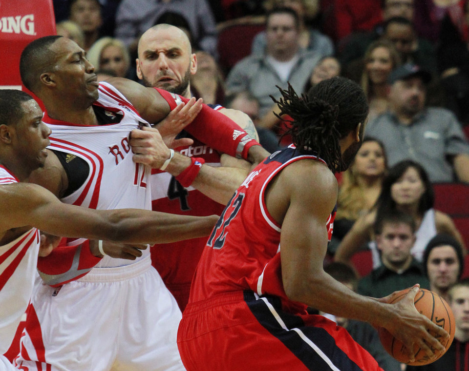 Photo - Houston Rockets center Dwight Howard, second from left, is grabbed by Washington Wizards center Marcin Gortat (4) as Wizards' forward Nene, right, goes to the basket guarded by Rockets forward Terrence Jones, left, during the second half of an NBA basketball game in Houston, Wednesday, Feb. 12, 2014. (AP Photo/Richard Carson)