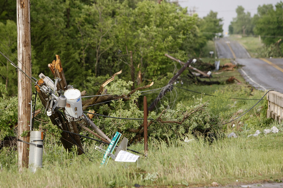 Power poles were snapped it two at Harrah Road and Reno Monday afternoon as a tornado moved through the area.  Photo by Hugh Scott, The Oklahoman