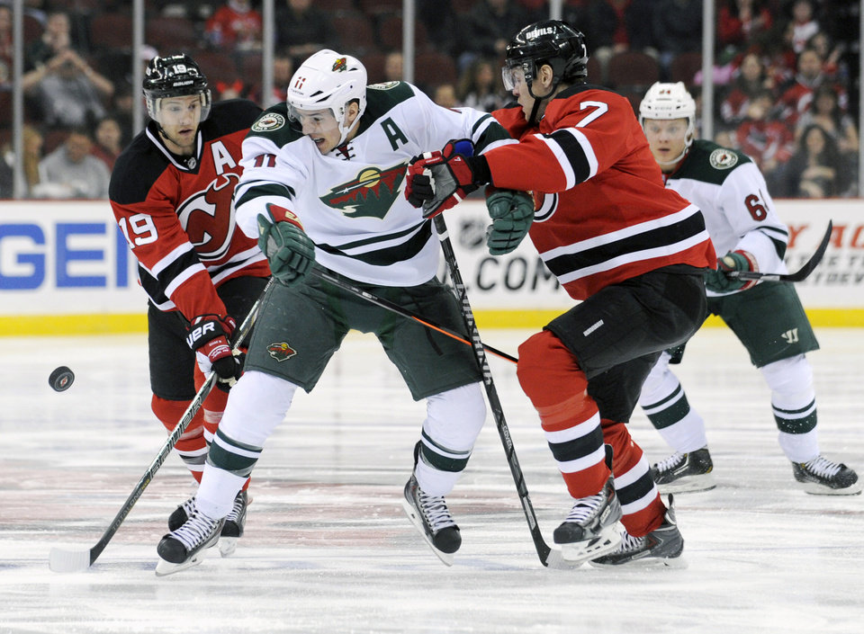 Photo - Minnesota Wild's Zach Parise is sandwiched by New Jersey Devils' Travis Zajac, left, and Mark Fayne, right, during the first period of an NHL hockey game Thursday, March 20, 2014, in Newark, N.J. (AP Photo/Bill Kostroun)