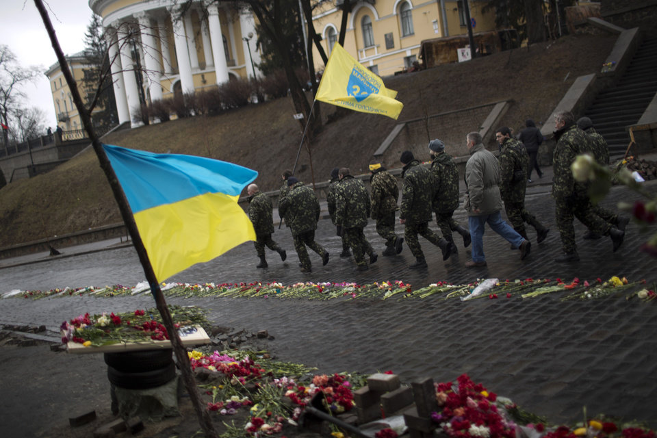 Photo - Ukrainian men wearing camouflage uniforms march along a street at a memorial for people killed during clashes with police at Kiev's Independence Square, Ukraine, Wednesday, March 5, 2014. Stepping back from the brink of war, Vladimir Putin talked tough but cooled tensions in the Ukraine crisis Tuesday, saying Russia has no intention