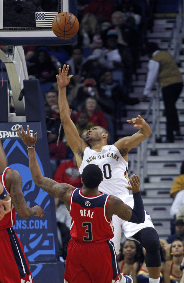 Photo - New Orleans Pelicans shooting guard Eric Gordon (10) is fouled as he goes to the basket against Washington Wizards shooting guard Bradley Beal (3) in the first half of an NBA basketball game in New Orleans, Wednesday, Jan. 8, 2014. (AP Photo/Gerald Herbert)