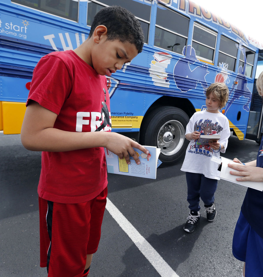 Kayden Carter, 9, and Erik Rundstrom, 8, look at books they selected from the Oklahoma City Thunder's Rolling Thunder Book Bus, which made a stop Tuesday at the Cleveland County YMCA's spring break camp. PHOTO BY STEVE SISNEY, THE OKLAHOMAN