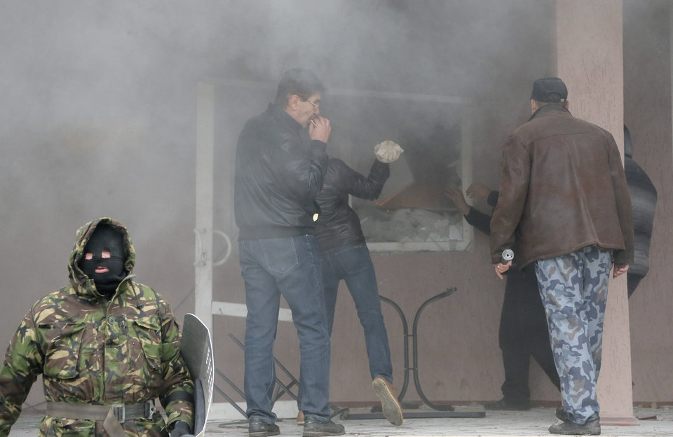 Photo - Pro-Russian men attack a police station in the eastern Ukrainian town of Horlivka Monday, April 14, 2014.  Several government buildings have fallen to mobs of Moscow loyalists in recent days as unrest spreads across the east of the country.  (AP Photo/Efrem Lukatsky)
