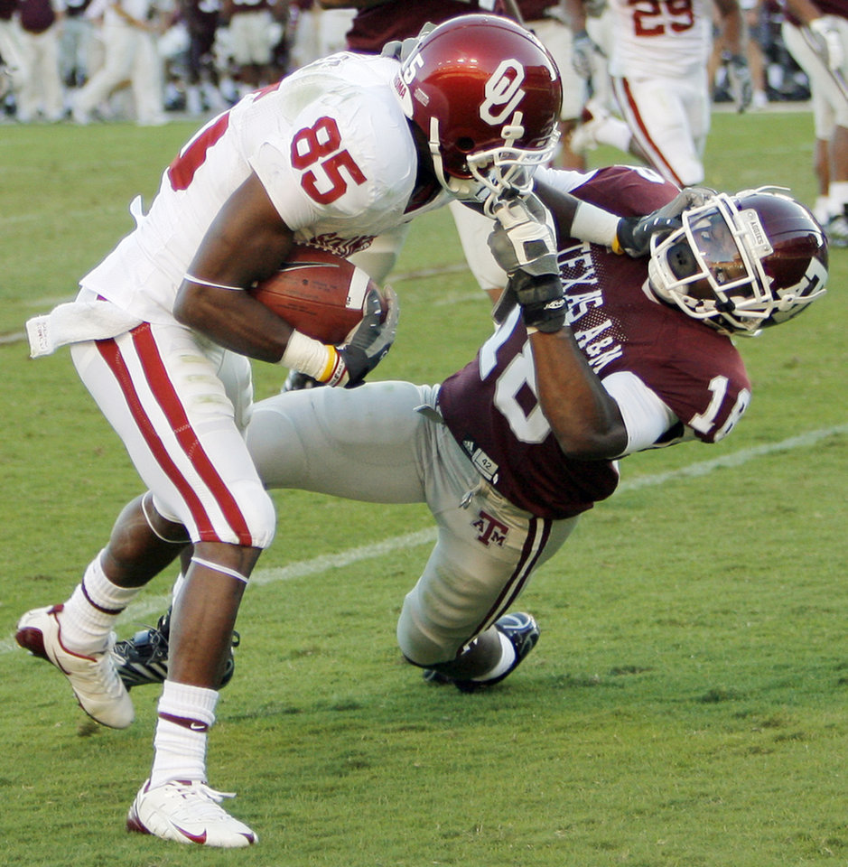 Photo - Texas A&M's Arkeith Brown pulls on the face mask of OU's Ryan Broyles in the first half during the college football game between the University of Oklahoma (OU) and Texas A&M University (TAMU) at Kyle Field in College Station, Texas, Saturday, Nov. 8, 2008. BY NATE BILLINGS, THE OKLAHOMAN