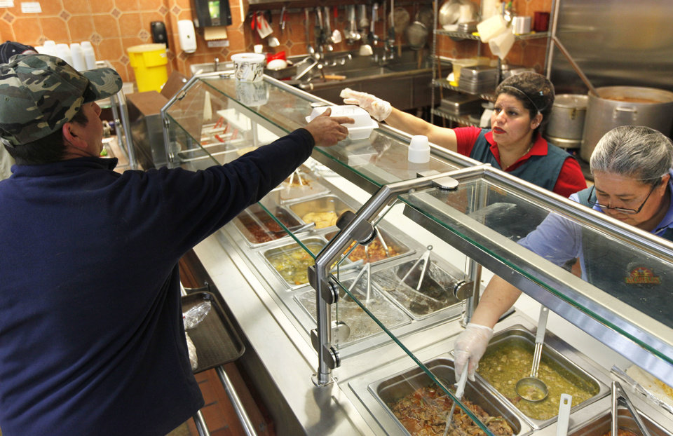 Photo - Maria Rodriguez hands a meal to a customer at Supermercado Morelos on Feb. 6 in Moore.  Photo by Paul Hellstern, The Oklahoman  PAUL HELLSTERN - Oklahoman