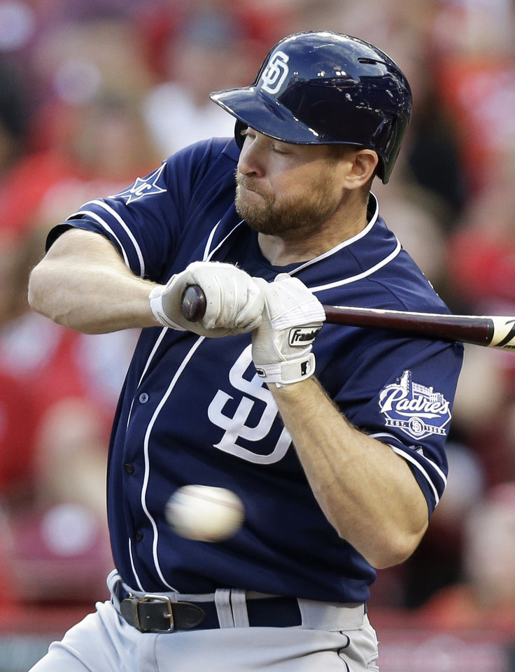 Photo - San Diego Padres' Chase Headley is hit by a pitch from Cincinnati Reds starting pitcher Mike Leake in the fourth inning of a baseball game, Tuesday, May 13, 2014, in Cincinnati. (AP Photo)