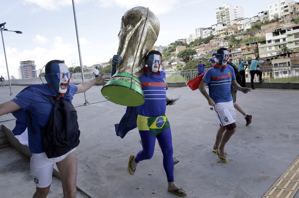 Photo - French soccer fans in costume run with a large replica of the World Cup trophy as they arrive to Arena Fonte Nova for their team's World Cup match with Switzerland in Salvador, Brazil, Friday, June 20, 2014. (AP Photo/Christophe Ena)