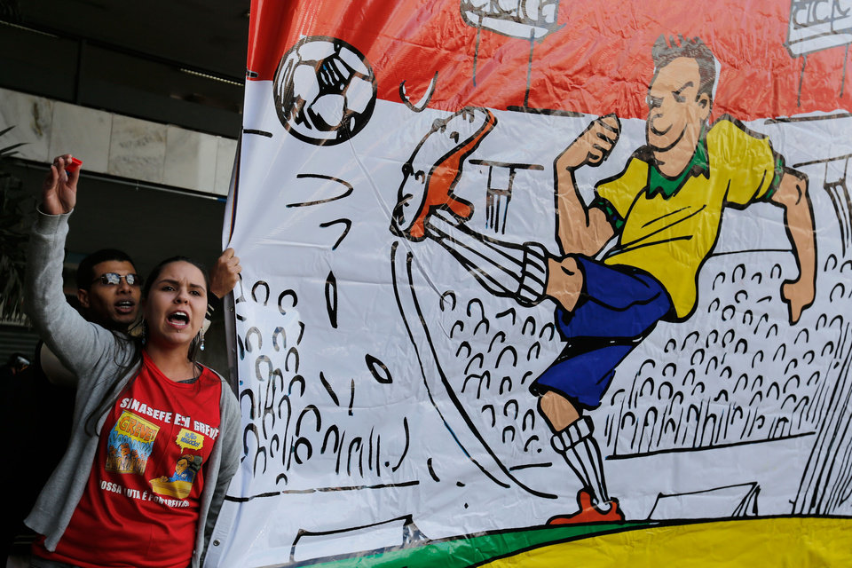 Photo - Demonstrators shout slogans during a protest against the World Cup, in Brasilia, Brazil, Sunday, June 15, 2014. Protesters are unhappy about the money spent on the FIFA 2014 Soccer World Cup, which they believe would have been better spent in improving the country's basic services.  (AP Photo/Eraldo Peres)