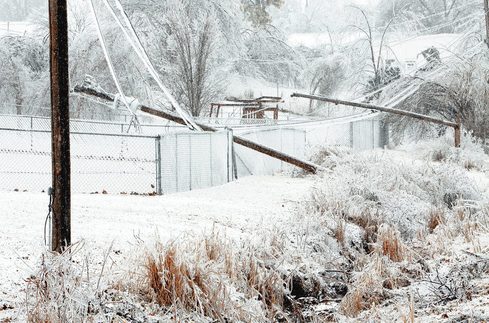 Above: Power poles lie over fences Friday in Purcell after the winter storm.  Photo by Steve Sisney, The Oklahoman