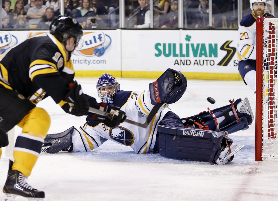 Photo - Boston Bruins' Reilly Smith (18) shoots wide of Buffalo Sabres' Matt Hackett (31) during the second period of an NHL hockey game in Boston, Saturday, April 12, 2014. (AP Photo/Michael Dwyer)