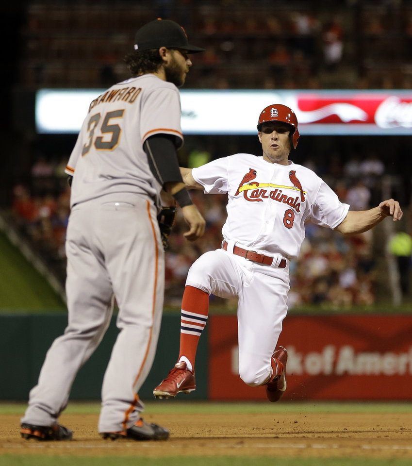 Photo - St. Louis Cardinals' Peter Bourjos, right, slides safely into third on a sacrifice bunt by Jaime Garcia as San Francisco Giants shortstop Brandon Crawford covers third during the fifth inning of a baseball game, Thursday, May 29, 2014, in St. Louis. (AP Photo/Jeff Roberson)