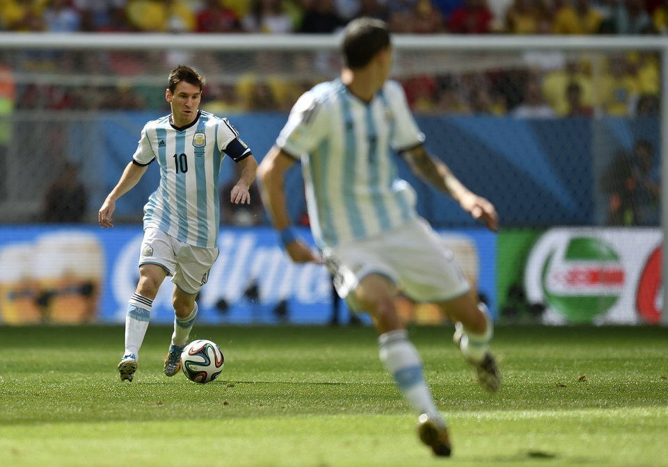 Photo - Argentina's Lionel Messi, left, runs with the ball during the World Cup quarterfinal soccer match between Argentina and Belgium at the Estadio Nacional in Brasilia, Brazil, Saturday, July 5, 2014. (AP Photo/Martin Meissner)