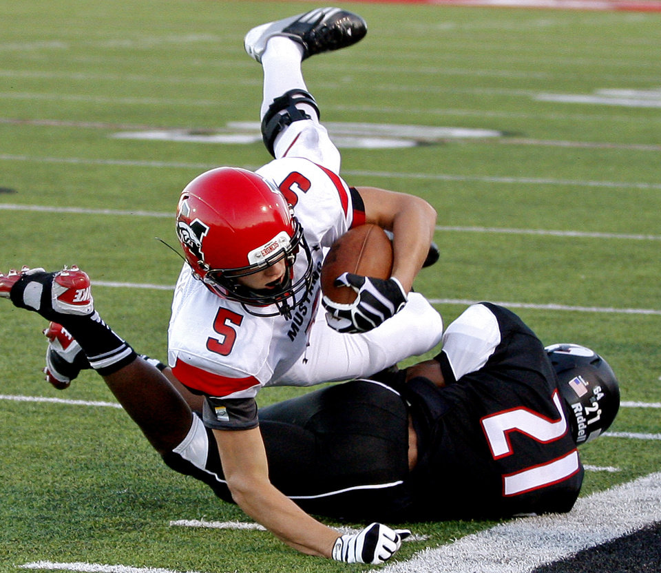 Photo - Mustang's Colton Hadlock leaps over Yukon's Matt Cammons during a high school football game in Yukon, Okla., Friday, August 31, 2012. Photo by Bryan Terry, The Oklahoman