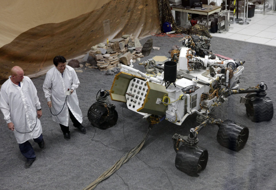 Photo -   FILE - In this file photo taken Thursday, Aug. 2, 2012, engineers work on a model of the Mars rover Curiosity at the Spacecraft Assembly Facility at NASA's Jet Propulsion Laboratory in Pasadena, Calif., After traveling 8 1/2 months and 352 million miles, Curiosity will attempt a landing on Mars the night of Aug. 5, 2012. (AP Photo/Damian Dovarganes, File)