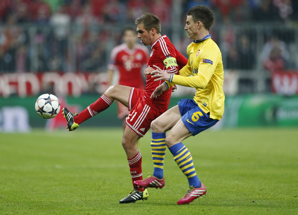 Photo - Bayern's Philipp Lahm, left, is challenged by Arsenal's Laurent Koscielny during the Champions League round of 16 second leg soccer match between FC Bayern Munich and FC Arsenal in Munich, Germany, Wednesday, March 12, 2014. (AP Photo/Matthias Schrader)
